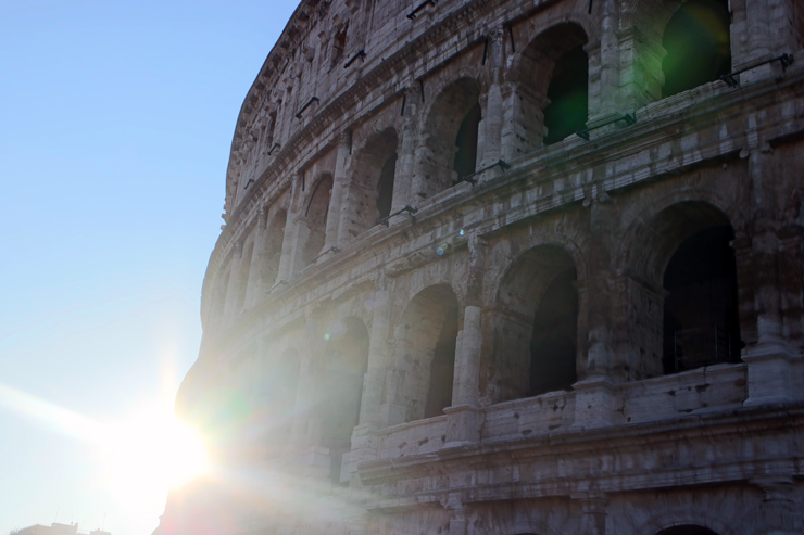 The rising sun behind the Colosseum